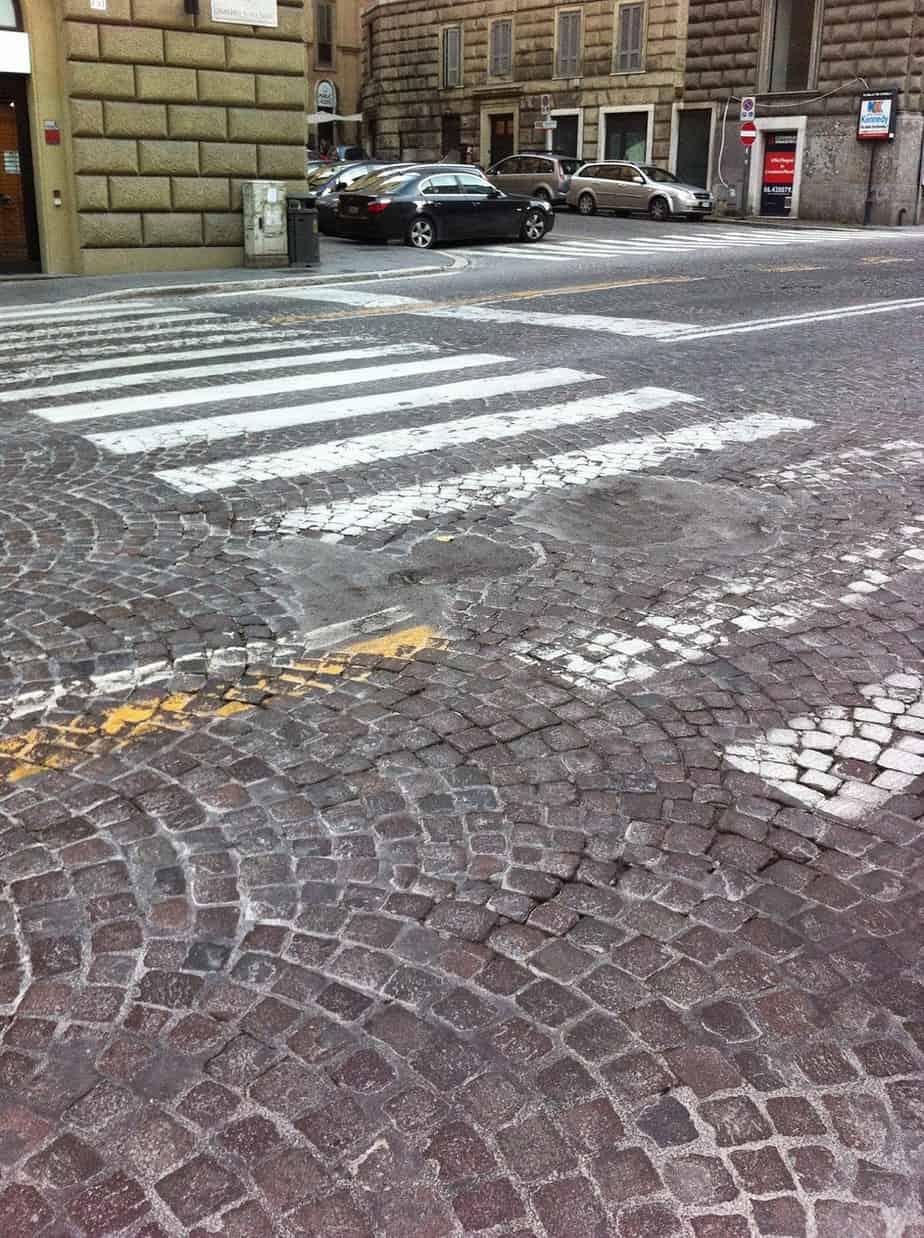 Una pavimentazione in cubetti deteriorata e trattata con sola sabbia e cemento