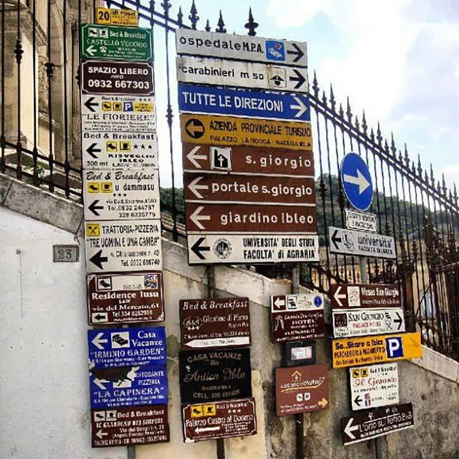 Esempio di segnaletica urbana sovrabbondante, poco leggibile, irregolare e impropriamente ricca di cartelli commerciali