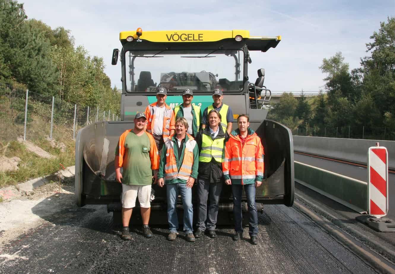La planarità e la tempistica dei lavori sono totalmente sotto controllo: la squadra di stesa, che nella foto è con Harald Zippe (Direttore di cantiere, ultimo a destra in prima fila) e Ewald Schemitsch (Responsabile Vendite della Wirtgen Österreich GmbH, secondo da destra in prima fila), è rimasta pienamente soddisfatta