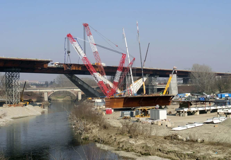 Il sollevamento con grandi gru delle ultime sezioni di impalcato sul fiume Lambro