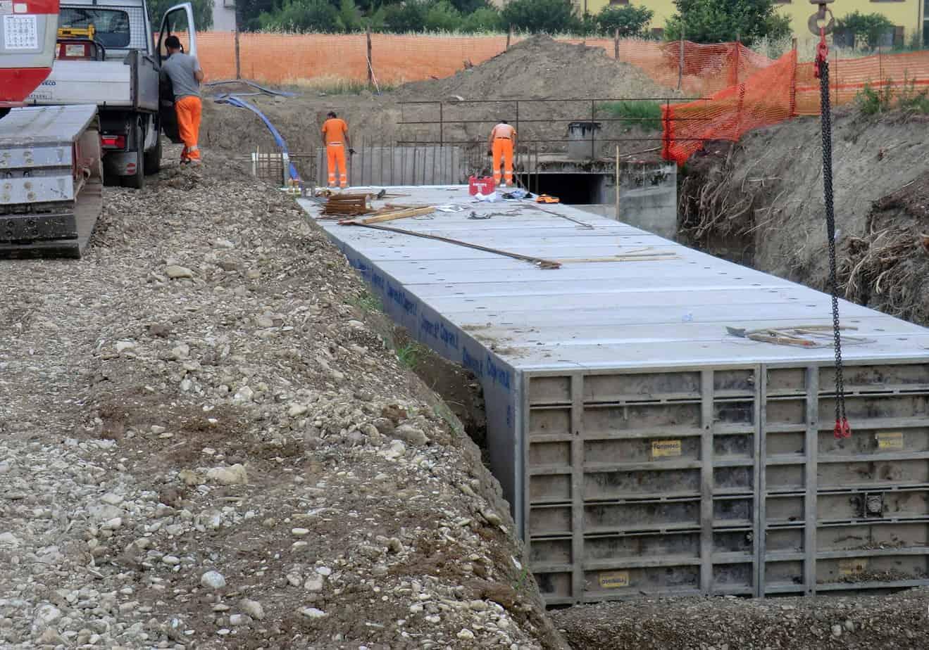 L'inizio della posa degli scatolari dal primo punto di collegamento gettato in opera, con il tamponamento per proteggere dai detriti portati da eventuali onde di piena