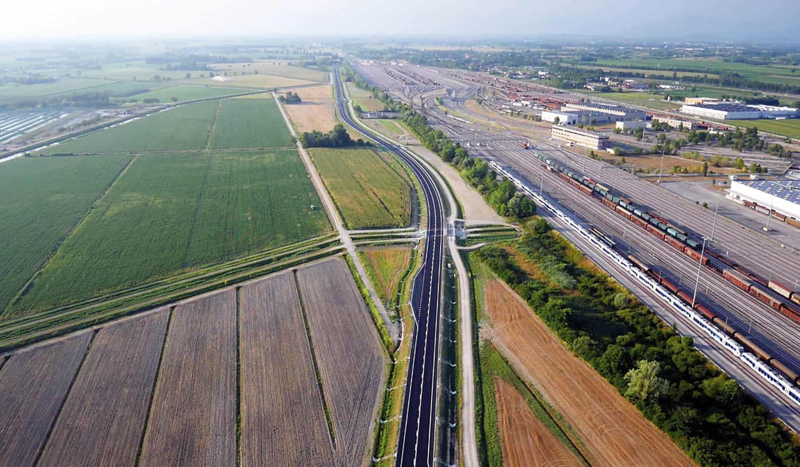 L'immagine dell'arteria stradale in prossimità dell'interporto ferroviario di Cervignano. In primo piano, un ponte delle opere minori su canale consortile