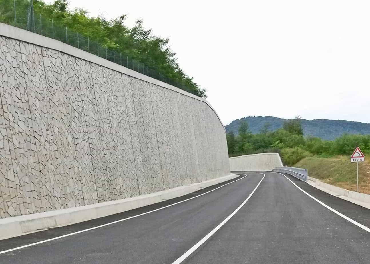 La paratia di pali di grande diametro, rivestita con lastre prefabbricate, lungo il tratto in affiancamento alla linea ferroviaria Arcisate-Stabio